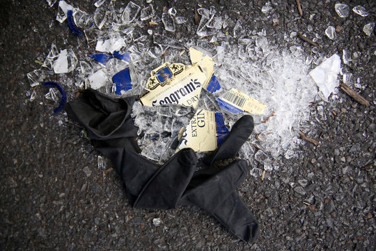 A discarded latex glove and broken gin bottle lie on the ground in a shopping center parking lot during the coronavirus disease (COVID-19) outbreak in Oxon Hill, Maryland