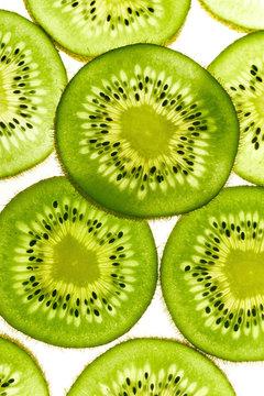 Macro shot of backlit kiwi fruit slices on white background. Top view layout
