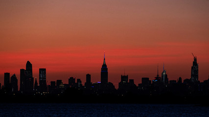 The Empire State Building and the Manhattan skyline are seen shortly after sunset from the Rockaway section of Queens, New York