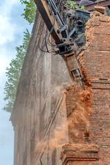 Excavator breaks an old brick wall.