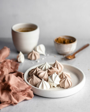 White and brown meringue cookies on a small, white dish next to a warm-colored napkin with fringed edges, with a coffee cup, a cup of brown sugar, and a rose gold spoon in the blurred background