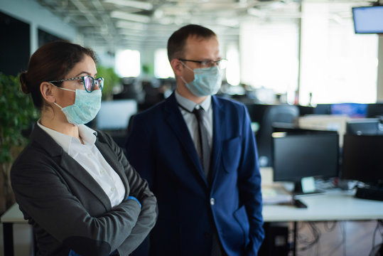 Colleagues in protective masks work in an open space office. A man and a woman in suits work at the workplace. Head and subordinate. European business people during a virus outbreak.