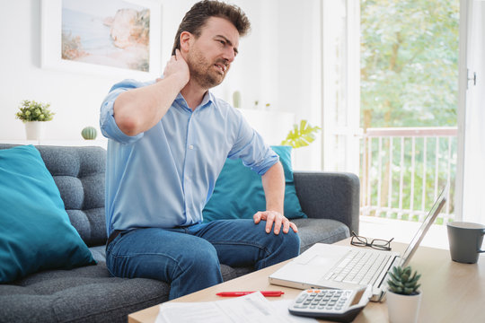 Young guy suffering from backache working from home