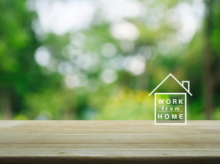 Work from home flat icon on wooden table over blur green tree in garden, Business social distancing online concept