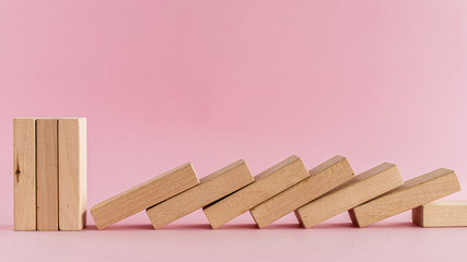 The wooden toys arranged in a horizontal row but the next others falling down on pink background for leisure activities concept