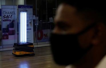 An autonomous mobile robot that disinfects surfaces with ultraviolet light, known as Sunburst UV Bot, passes a security guard at Northpoint City shopping mall amid the coronavirus disease (COVID-19) outbreak in Singapore