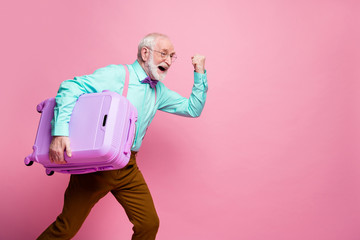 Profile side photo delighted crazy retired man win relax summer lottery hold big lugagge run fast terminal check-in wear teal turquoise shirt brown pants isolated pink color pastel background
