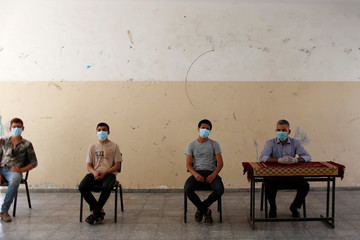 Palestinian students receive their certificate as preventive measures against COVID-19 are taken, in Gaza