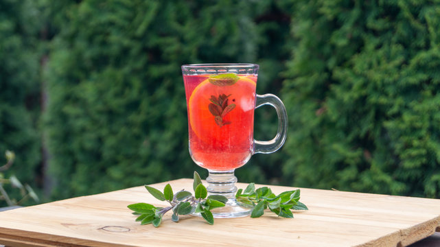 glass goblet with cold cocktail on a wooden table in the garden on a background of green plants