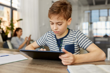 children, education and school concept - happy student boy with tablet pc computer learning at home