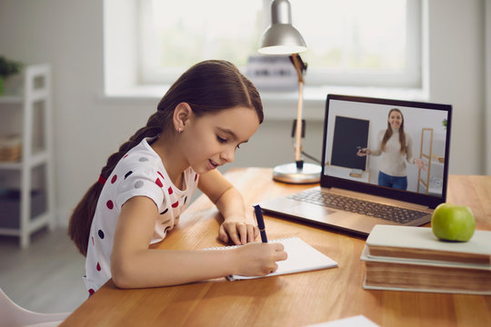 Online training. The teacher teaches the child a video call chat classroom video conferencing. Little girl teach a lesson using a laptop with sitting at a table at home.