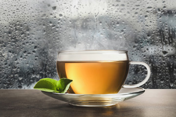 Glass cup of hot green tea near window on rainy day Fotobehang