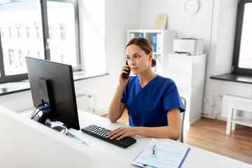 medicine, technology and healthcare concept - female doctor or nurse with computer calling on phone at hospital