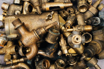 Brass scrap metal: taps, tees, plugs and various plumbing parts, spare parts. Against the background of a copper sheet. Close-up.