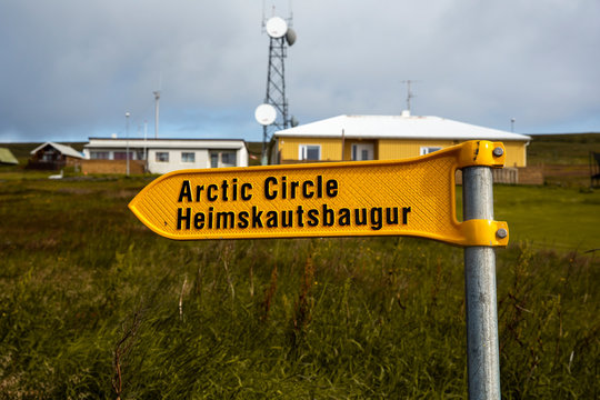 landscape with the port of the island of grimsey in the north of iceland, off the arctic circle. A yellow sign indicates the direction to follow towards the crossing of the polar circle.