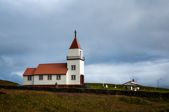 Landscape on Grimsey Island in northern Iceland beyond the Arctic Circle. A white church with a red roof is visible, surrounded by a cemetery with white tombs