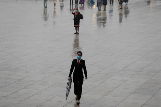 Woman takes pictures outside the Great Hall of the People after the opening session of CPPCC in Beijing
