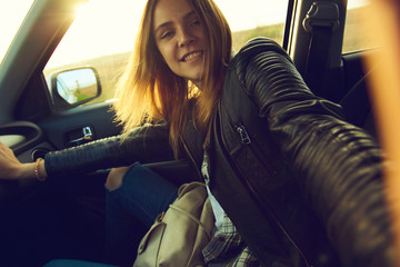A girl making selfie portrait in the car with view