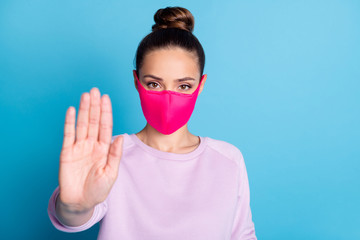 Stay away. Closeup photo of pretty lady keep social distance raise palm arm don't let people contacting her wear protect bright face mask sweater isolated blue color background