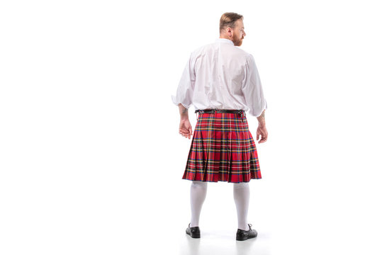 back view of Scottish redhead man in red kilt on white background
