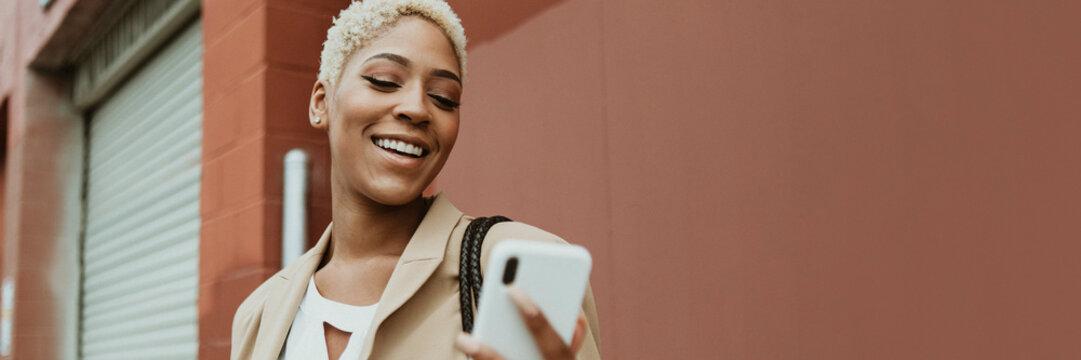 Happy black businesswoman using her smartphone