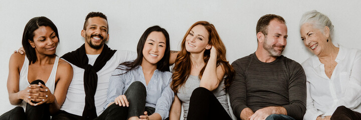 Group of cheerful diverse people sitting on a floor in a white room