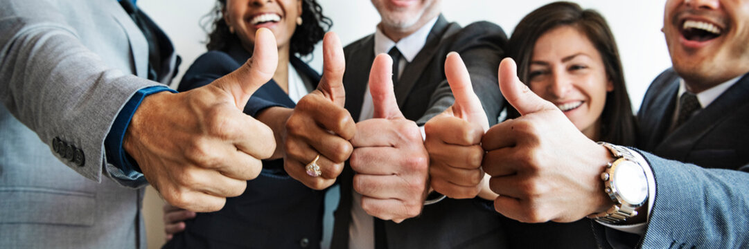 Businesspeople doing a thumbs up together