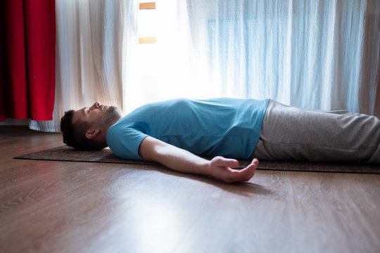 Young man meditating on a floor and lying in Shavasana pose at his living room. Stay home and do yoga relax, meditating concept,