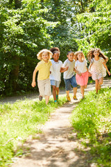 Group of kids running together over meadow