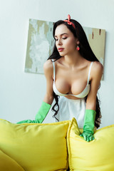 Sensual woman in bra and rubber gloves standing near couch at home