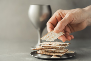 Hands with chalice and communion matzo bread, wooden cross on grey background. Christian communion for reminder of Jesus sacrifice. Easter passover. Eucharist concept. Christianity symbol and faith