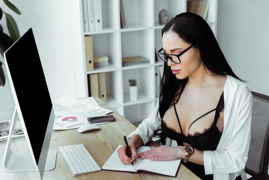 Beautiful secretary in bra and eyeglasses writing on notebook in office