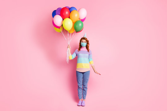 Full length photo of pretty lady social distance arrange birthday party best friend stay home hold many air balloons wear protect face mask sweater jeans shoes isolated pink color background