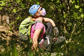 Woman mountaineer with helmet, backpack, and medical mask, enjoys the fresh nature air in a forest. Concept of Coronavirus (Covid-19) restrictions being eased and people returning to nature.