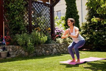 Young attractive brunette standing on the mat in her backyard in Chair position.