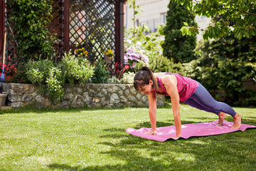 Young attractive yogi woman in plank posture. Backyard exterior.