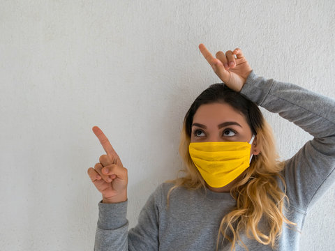 Young woman with homemade mask pointing, stop virus, save herself, modern lifestyle