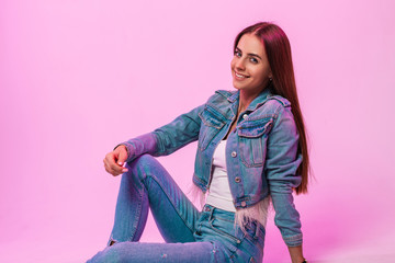 European joyful young woman fashion model with sweet smile in fashionable blue jeans clothing sits...