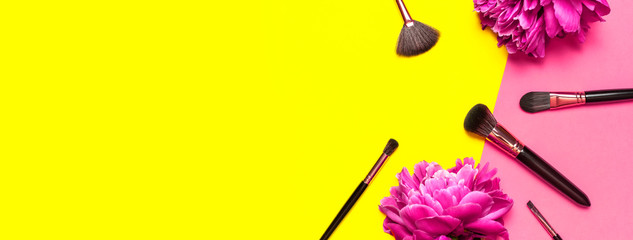 Professional Different makeup brushes with pink spring peonies flowers on yellow pink background flat lay top view copy space. Beauty product, makeup, women's accessory, fashion. Cosmetic makeup Set
