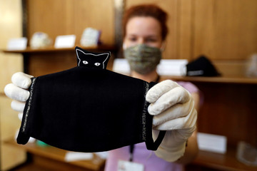 A worker prepares a face mask exhibition in Prague