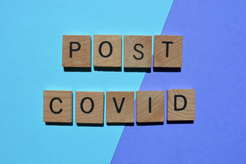 Post Covid, phrase in wooden letters on blue. Creative Concept