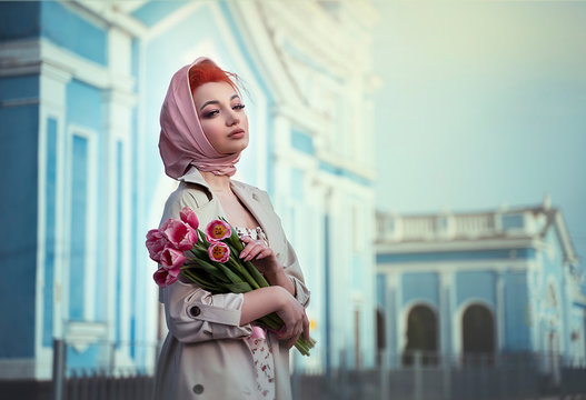 A woman in a spring dress and coat, like an old-style, holds a bouquet of pink flowers in the old town. Romantic retro girl walks around the city.