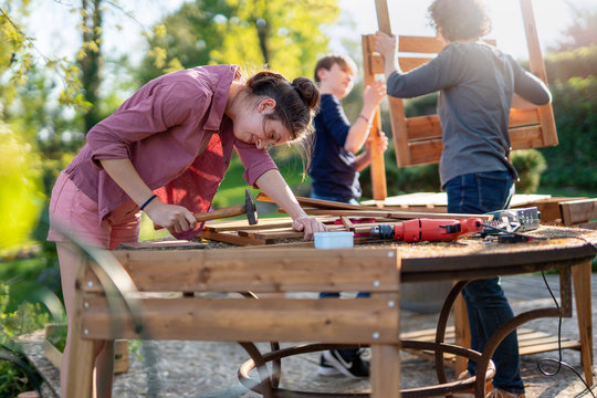 A teenage girl helps her family to build wooden planters for their permaculture vegetable garden