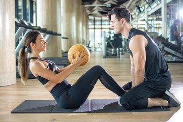 Fitness couple doing exercises with a medicine ball at gym.