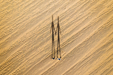 Aerial view of two persons shadows holding hands in desert terrain near Corralejo dunes in Fuerteventura island.