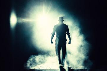 Fotomurales - Full Length Of Silhouette Man Walking Against Bright Light At Night
