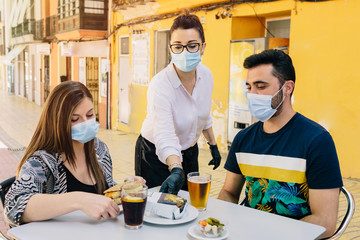 Obraz Clients with masks on the terrace of a bar in Spain attended by a waiter with gloves and masks. Social distancing during phase one of de-escalation. Coronavirus - fototapety do salonu