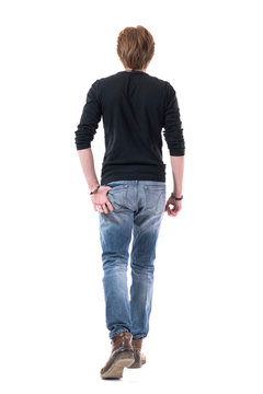 Cool handsome young man with thumb in back pocket walking away and leaving from behind. Full body length isolated on white background.
