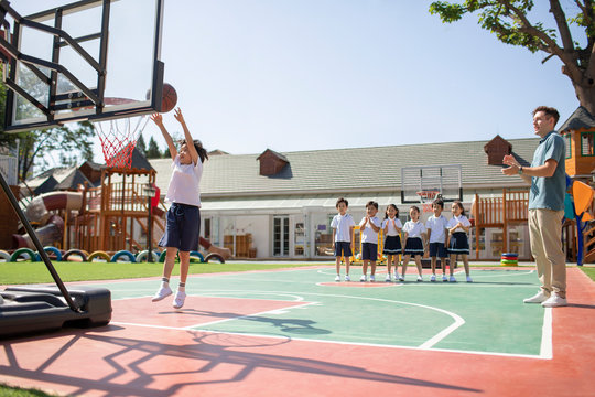 Foreign teacher and children playing basketball in playground