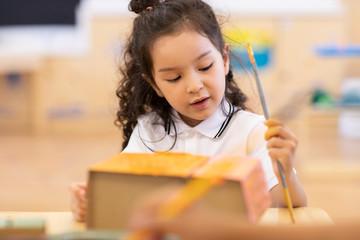 Little girl having art class in classroom